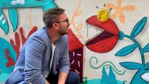 Paweł Lisowski obok eko muralu malowanego w ramach Brave Kids farbami antysmogowymi